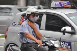 Một người đàn ông trên phố Xã Đàn giờ tan tầm phải lấy tay che cổ vì lạnh