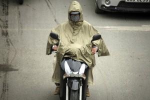 Một người đàn ông mặc áo mưa để tránh rét