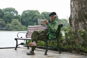 Một cụ gia đọc báo ngồi hưởng thụ cái lạnh ngay cạnh bờ hồ